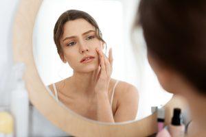 mlada žena koja se ogleda u ogledalu, proveravajući kožu lica